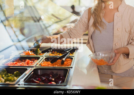 Young woman at salad bar in grocery store market - Stock Photo