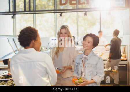 Young women friends at salad bar in grocery store market - Stock Photo
