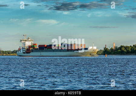 freight ship on sunset light going from port in Riga,Latvia, industrial transportation background - Stock Photo