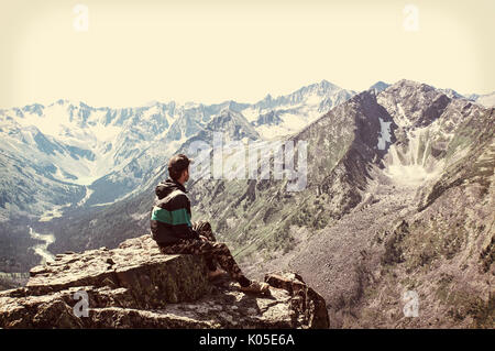Man sit on sharp cliff above valley in rocky mountains park and watch into landscape. The tourist has conquered - Stock Photo