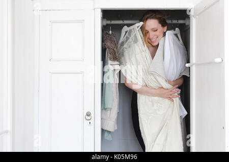 A woman is overwhelmed in closet of messy clothes on a white background - Stock Photo