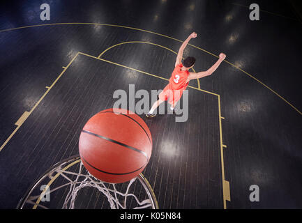 Confident young male basketball player shooting the ball and gesturing, celebrating - Stock Photo