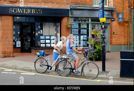 senior couple on bicycles looking in estate agents windows - Stock Photo