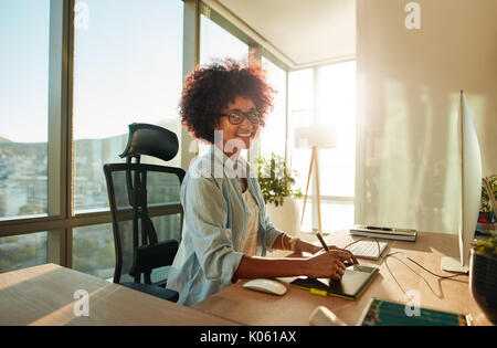 Portrait of creative young woman working in office with graphic tablet. African female designer working at her desk - Stock Photo