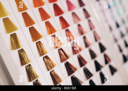 Closeup of hair samples with different color shades on a card. Hair color choice chart on display at salon. - Stock Photo