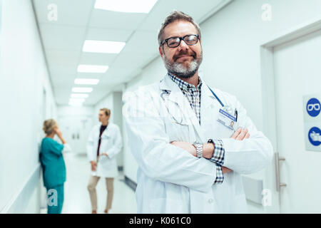 Portrait of positive doctor standing in hospital hallway with his arms crossed. Mature physician with colleagues - Stock Photo