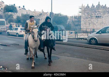 Palestinian youths ride horses near Damascus Gate - one of the entries to the Old City of Jerusalem, annexed by - Stock Photo