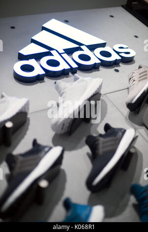 Munich, Germany. 21st Aug, 2017. The logo of sporting goods company Adidas on a wall above Adidas shoes in a store - Stock Photo