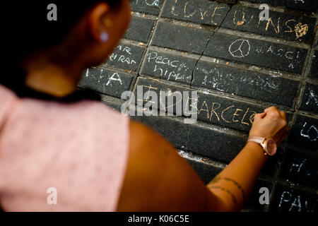Barcelona, Catalonia, Spain. 21st Aug, 2017. A woman writtes a message on the floor of Las Ramblas of Barcelona the same day that Younes Abouyaaqoub, identified as driver of van that sped down Las Ramblas on Thursday, has been shot dead by Catalan police officers in the village of Subirats. Credit: Jordi Boixareu/ZUMA Wire/Alamy Live News