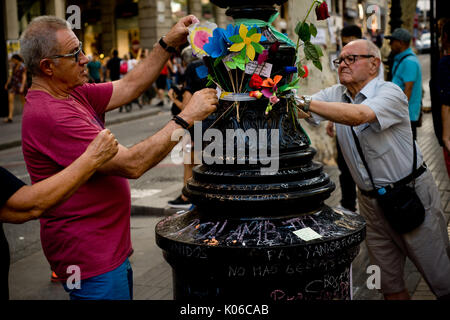 Barcelona, Spain. 21st Aug, 2017. Two men place flowers at a lamppost of Las Ramblas of Barcelona in memory of terror attack victims the same day that Younes Abouyaaqoub, identified as driver of van that sped down Las Ramblas on Thursday, has been shot dead by Catalan police officers in the village of Subirats. Credit: Jordi Boixareu/Alamy Live News