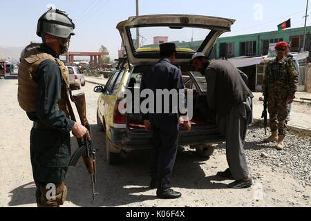 Ghazni, Afghanistan. 22nd Aug, 2017. An Afghan security force member checks a vehicle at a security checkpoint in - Stock Photo