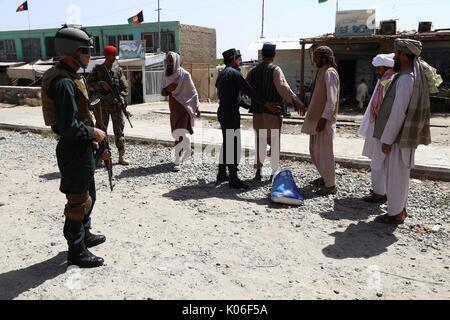 Ghazni, Afghanistan. 22nd Aug, 2017. An Afghan security force member checks a man at a security checkpoint in Ghazni - Stock Photo