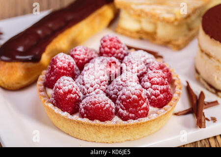close up shot of Delicious raspberry mini tarts with fresh raspberries and icing sugar - Stock Photo