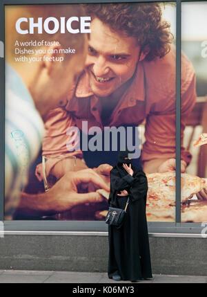 Outside a Brighton shopfront stands a Muslim woman wearing a burka - Stock Photo