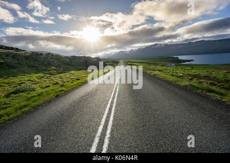 Iceland - Magic moment over straight highway between green fields next to fjord - Stock Photo