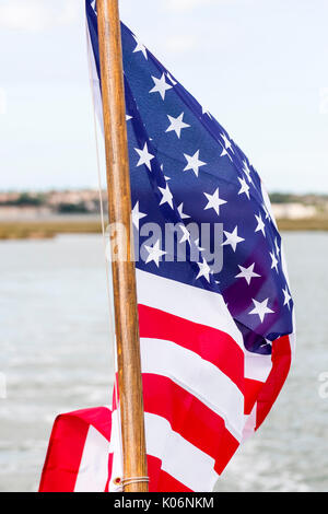 American flag fluttering from stern of boat. Close up, river behind flag. - Stock Photo