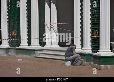 Man using power grinder on historic building in Perterhof, Russia - Stock Photo