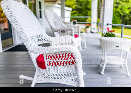 Front porch of house with white rocking chairs on wooden deck - Stock Photo