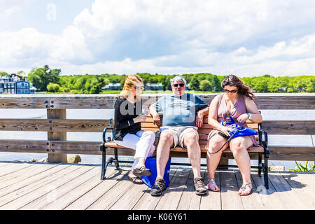 Kennebunkport, USA - June 10, 2017: Sidewalk street in downtown village during summer day with people sitting on - Stock Photo