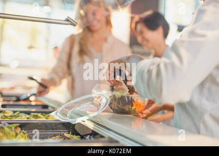 Young woman serving salad at salad bar in grocery store market - Stock Photo