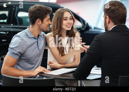 Confident young salesman explaining all the new car features to the young attractive owners - Stock Photo