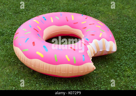 Inflatable swim ring in shape of donut on the grass. Summer vacations theme. - Stock Photo