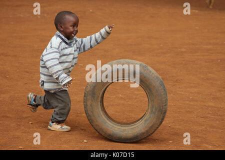 Child playing with tire, near Eldoret, Kenya, Kalingen tribal area - Stock Photo