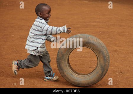 Child playing with tire, near Eldoret, Kenya, Kalingen tribal area - Stock Photo