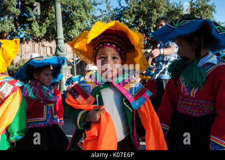 A group of children wearing Quechua ponchos and montera hats prepare for dance competition during Corpus Christi - Stock Photo