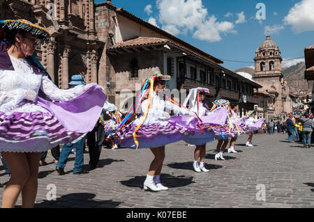 A dance troupe whirls along a cobbled street in the historic centre of Cusco during traditional festivities of Corpus - Stock Photo