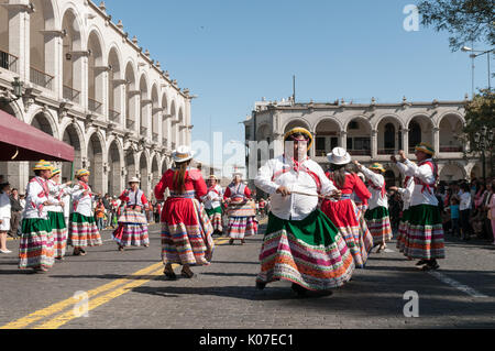 A group of farmers dressed in traditional clothing dances along a cobbled street near Plaza de Armas, Arequipa, - Stock Photo
