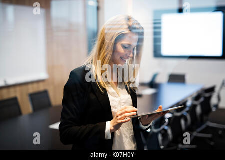 Portrait of beautiful blonde businesswoman holding tablet - Stock Photo