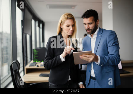 Portrait of attractive business partners using tablet - Stock Photo