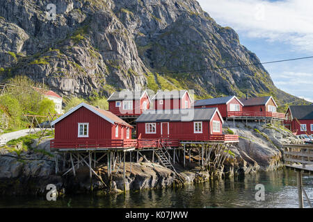 Red wooden rorbus fishermen's huts and buildings on stilts by sea in fishing village of Å, Moskenes, Moskenesøya - Stock Photo
