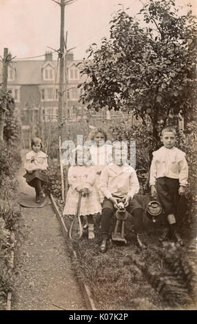 Five siblings playing in their suburban garden.     Date: circa 1910 - Stock Photo