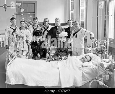 Friends and family visiting a patient, Brooklyn Navy Yard Hospital, New York City, USA     Date: 1901 - Stock Photo