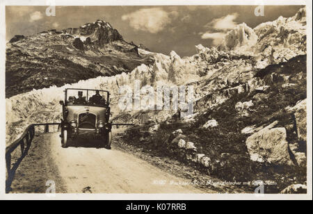 A Saurer open top Post Bus (Swiss rural bus service) navigating the winding Furkastrasse which passes the Rhone - Stock Photo
