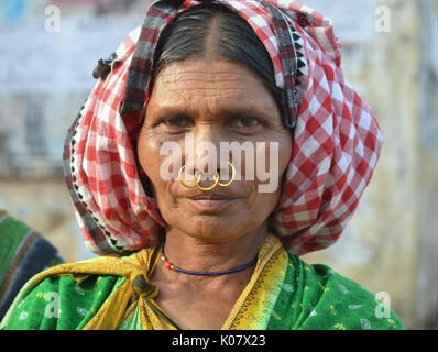 Elderly Indian Adivasi market woman with three golden nose rings. - Stock Photo