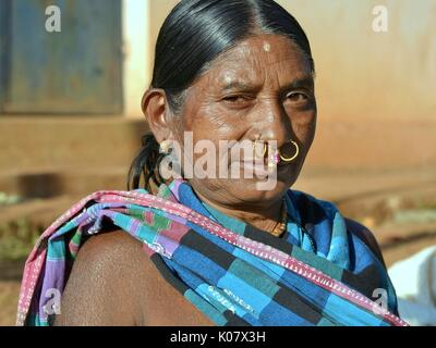Elderly Indian Adivasi market woman with two golden nose rings, one piece of precious gold-and-gemstone nose jewellery - Stock Photo