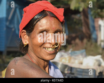 Elderly Indian Adivasi market woman with two golden nose rings and distinctive tribal earrings. - Stock Photo
