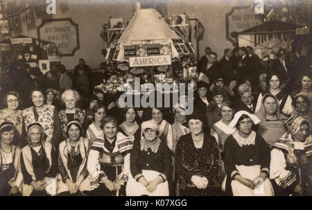 Group of women in national costume, and others in everyday costume, in a church hall, possibly in Harlesden, NW - Stock Photo