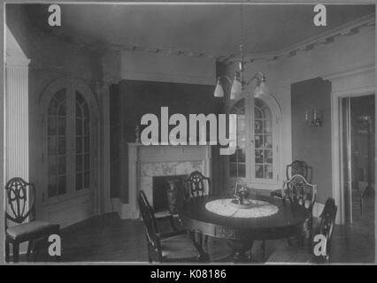 Photograph of a Roland Park dining room in Baltimore, with a round wooden table and wooden chairs around it, with - Stock Photo