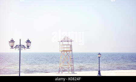 Retro old film stylized picture of a lifeguard tower on an empty beach. - Stock Photo