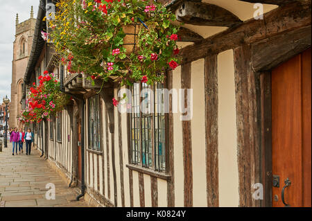 Half timbered almshouses decked out with colourful hanging baskets in Stratford upon Avon - Stock Photo