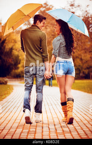 Beautiful lovely couple with umbrellas enjoying while walking in the rain through the park in autumn colors. Rear - Stock Photo