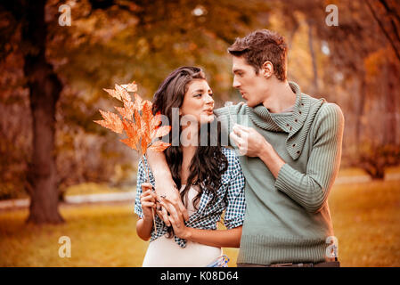 Beautiful lovely couple walking and enjoying in the park in autumn colors. - Stock Photo