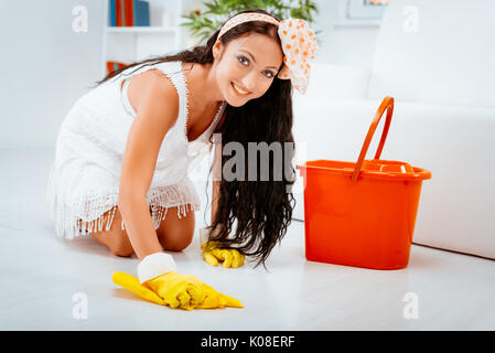 Young beautiful maid scrubbing floor. - Stock Photo