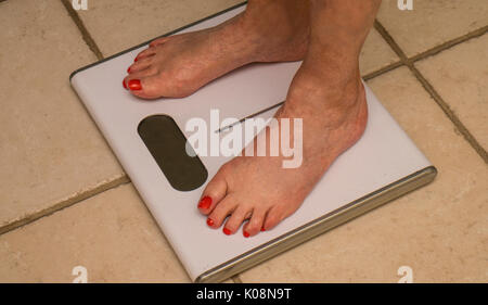 elderly woman standing barefoot  on a bathroom scale and measuring her weight - Stock Photo