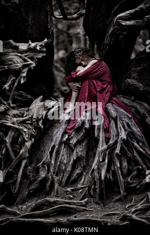 Beautiful young woman in a red dress curled up like a baby inside the root system of an old dead tree in a forest - Stock Photo
