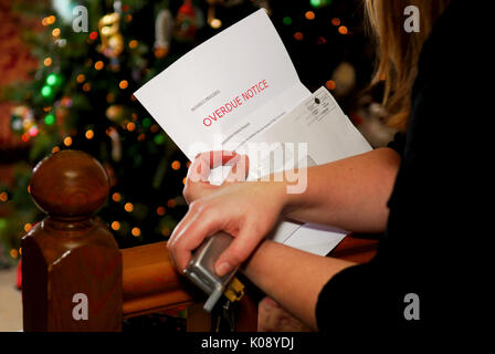 A woman holds an overdue notice, Christmas tree in background. - Stock Photo